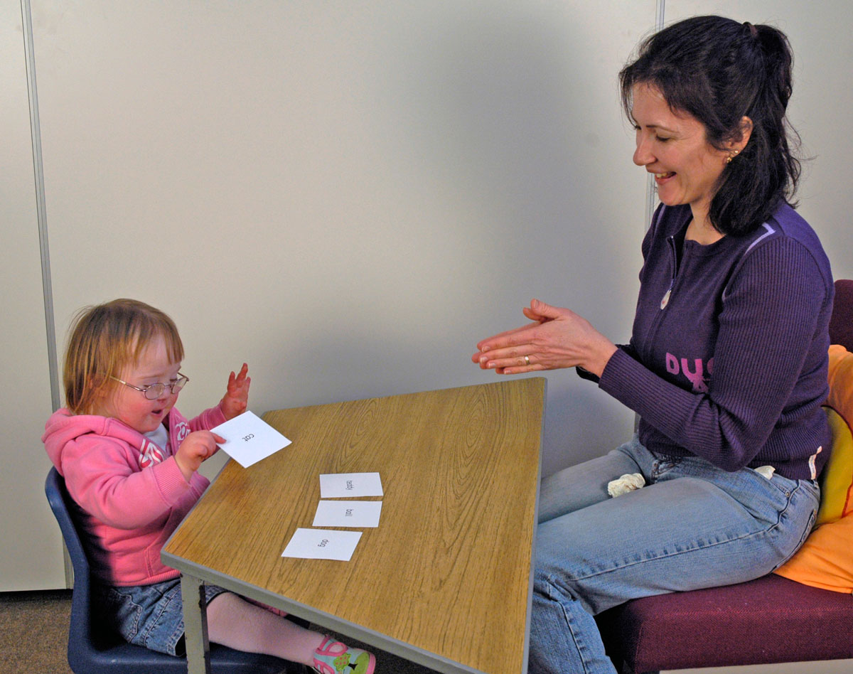 Picture of a child with Down syndrome selecting sight words