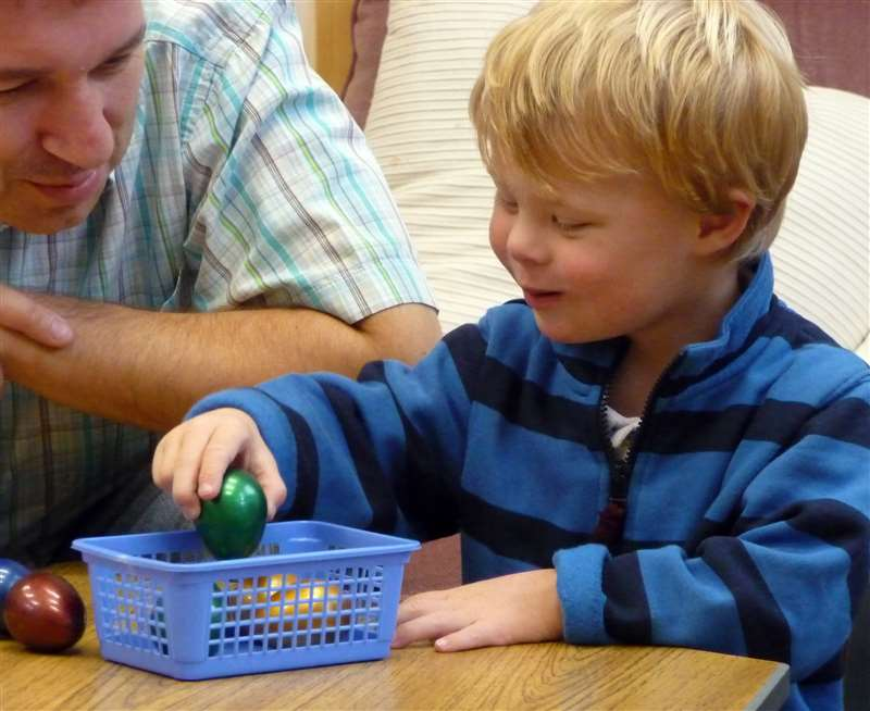 A photograph of a boy with Down syndrome counting objects