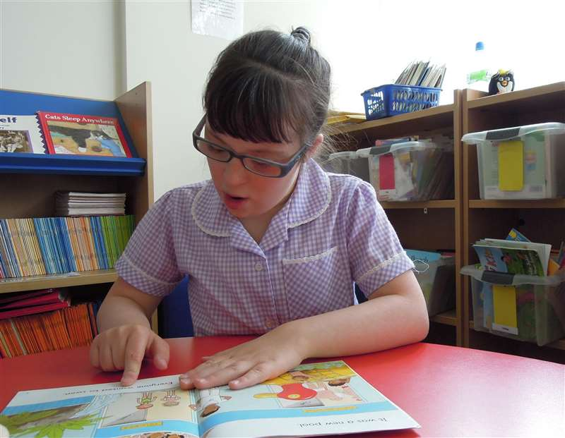 A photograph of a girl with Down syndrome reading a book