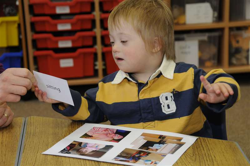 Picture of a child with Down syndrome learning to read