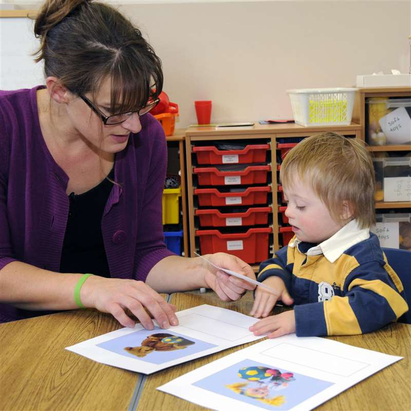 A child with Down syndrome learning vocabulary by matching pictures