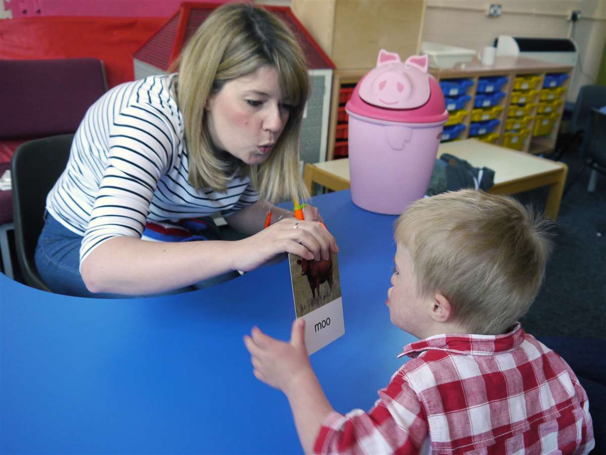 A photograph of child with Down syndrome learning to say whole words