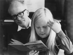 A photograph of Leslie Duffen watching his daughter Sarah read a book